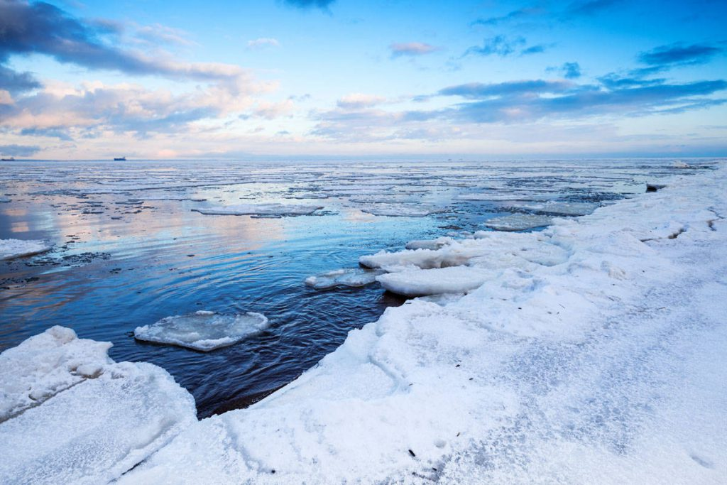 Winter coastal landscape with floating ice fragments on still water. Gulf of Finland, Russia