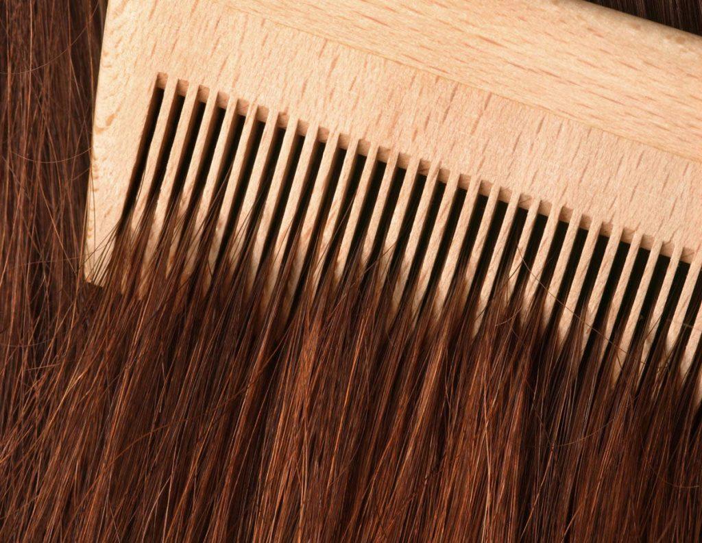 A comb running through long brown hair.
