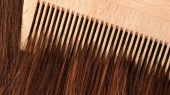 A comb running through long brown hair.