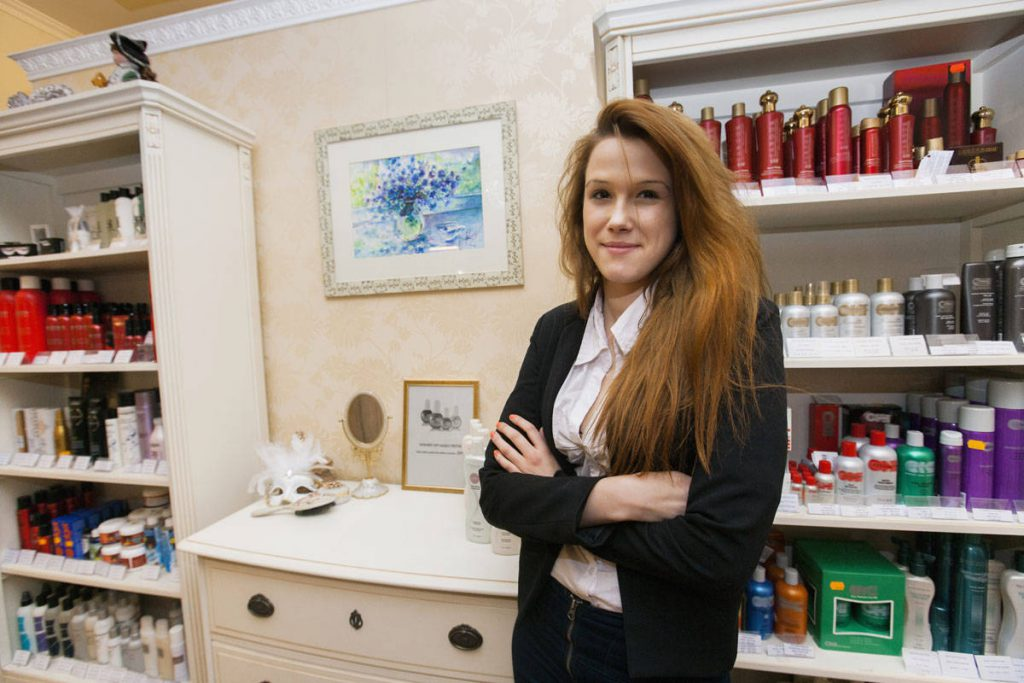 Portrait of confident female hairstylist in beauty salon
