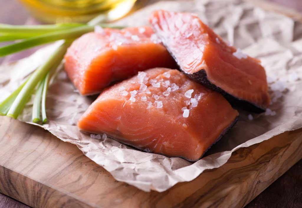Raw red fish fillet with sea salt over wooden board, selective focus