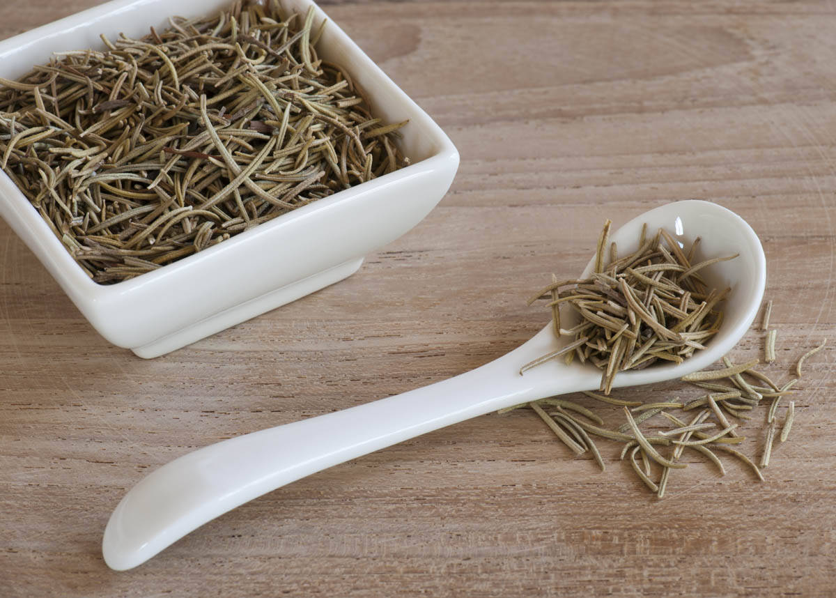 A Spoon and Dishful Of Dried Aromatic Rosemary Leaves, Up On A Wooden Work Surface