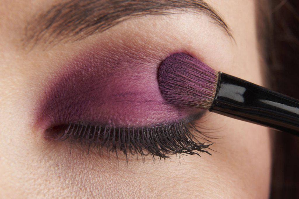 woman applying eye make-up with brush on white background