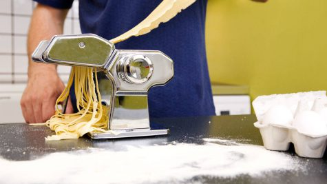 Fettuccine coming out of a manual pasta machine