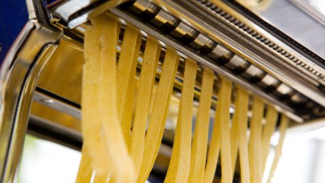 Fettuccine coming out of a manual pastamachine - shallow depth of field with focus on the pasta